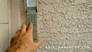 entering garage access code on keypad with finger